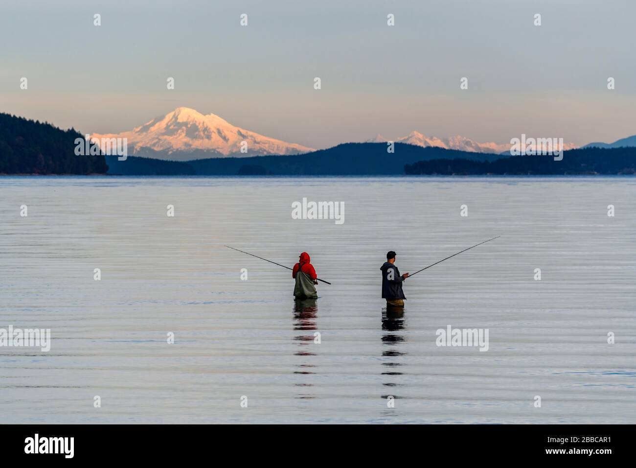 Two men ocean fishing at Cherry Point Beach near Cowichan Bay, British Columbia.  Mt. Baker in Washington State is in the background. Stock Photo