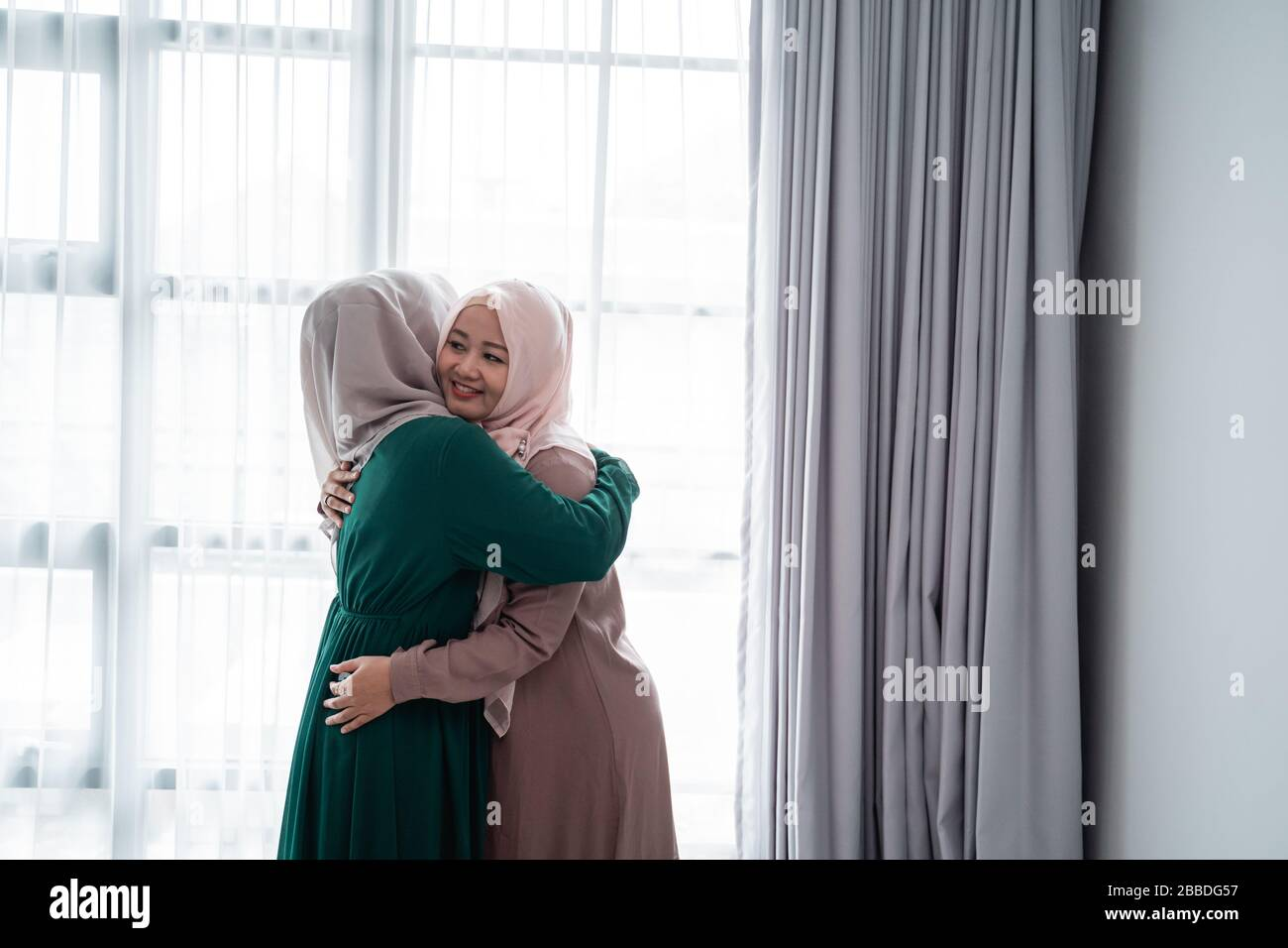 muslim hijab woman happily entrace home opens the door meets and hug her sister Stock Photo