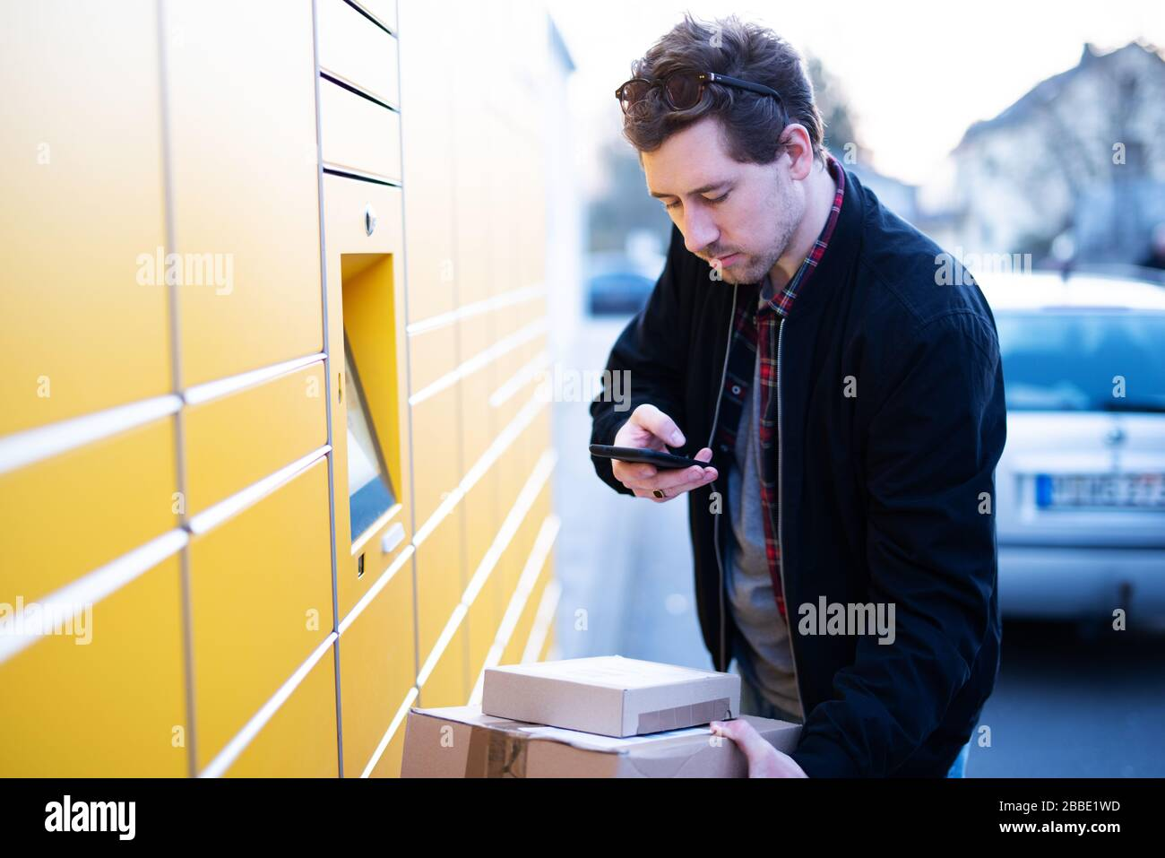 A man brings packages to a packing station or picks them up Stock Photo