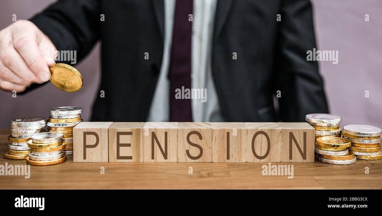 A pensions concept of a businessman saving for his pension by adding money from his salary, savings, wages and income Stock Photo