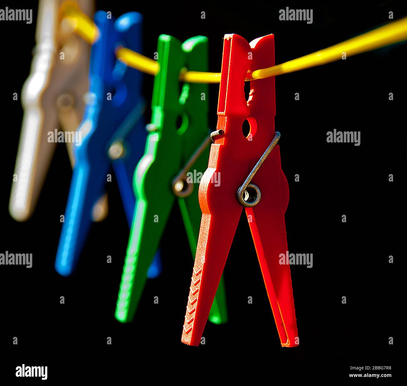 primary coloured pegs on line brightly lit on dark background Stock Photo