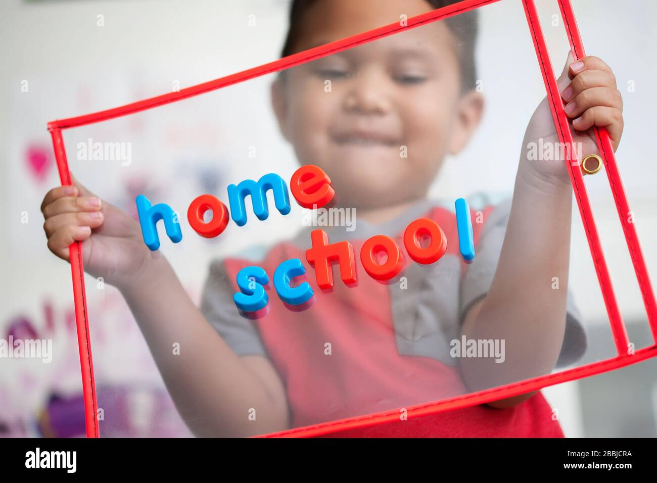 A 4 year old boy with a smile on his face is happy to start home school. Stock Photo
