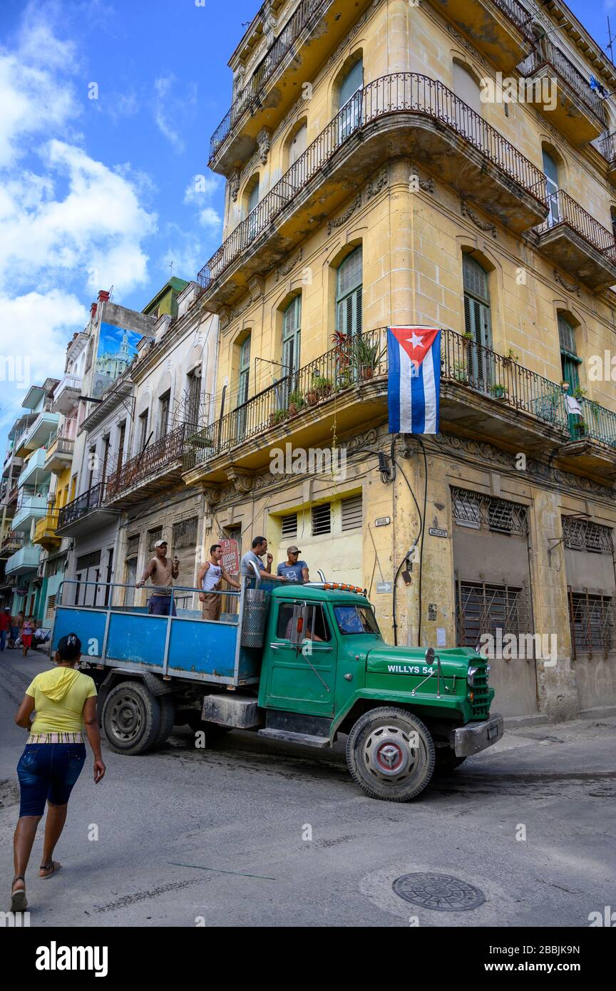 Work truck and building and flag at Brasil and Aguacate, Havana, Cuba Stock Photo