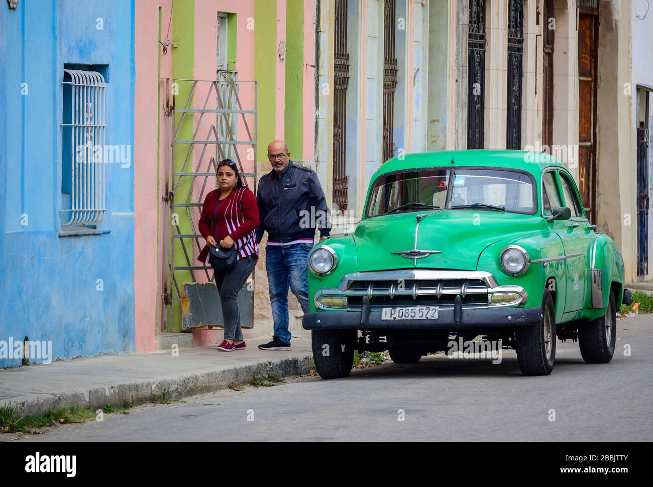 Old Chevrolet and passing couple, Havana, Cuba Stock Photo