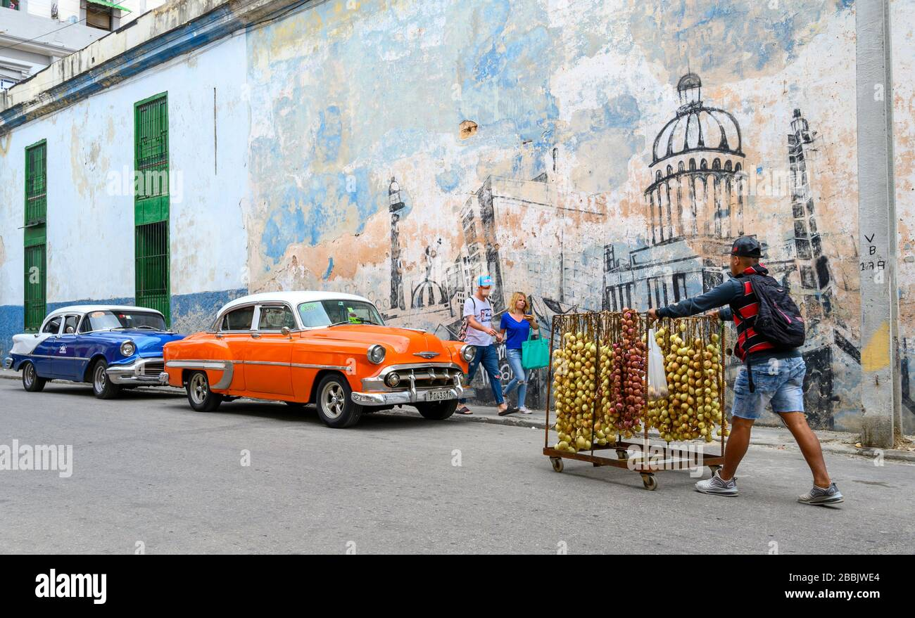 Old American Cars and wall mural of Havana, Cuba Stock Photo