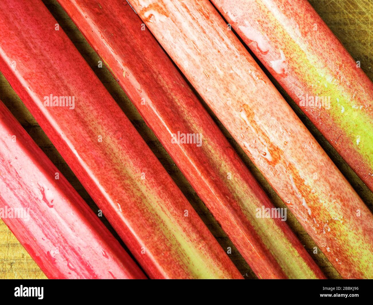 Fresh homegrown rhubarb stalks on a wooden chopping board Stock Photo