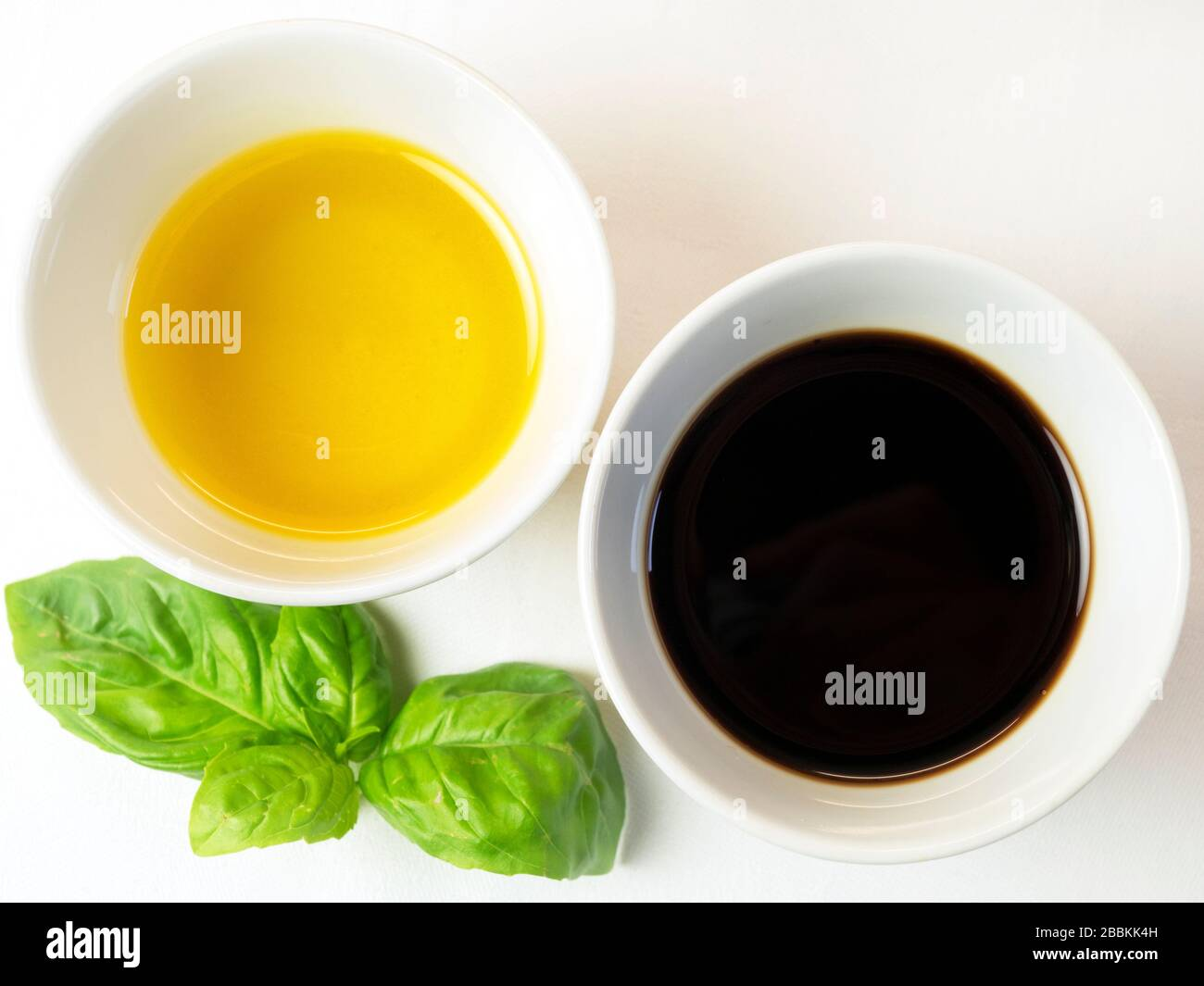 A bowl of Yorkshire cold pressed extra virgin rapeseed oil and a bowl of balsamic vinegar with a sprig of basil on a white tablecloth Stock Photo