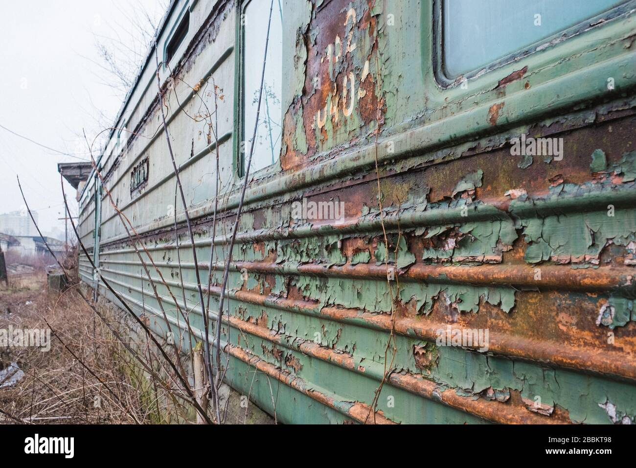 old rusty weathered peeled paint of an old wagon. Blue abandoned railway carriage. Old railwaystation Stock Photo