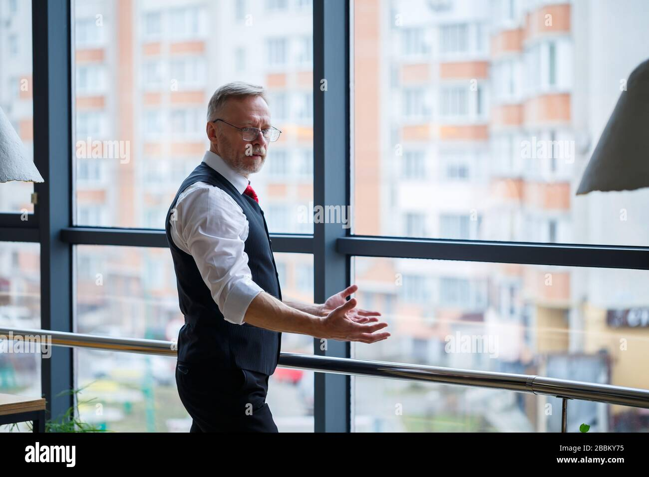 Smiling happy managing director thinks about his successful career development while stands in his office near the background of a window with copy sp Stock Photo