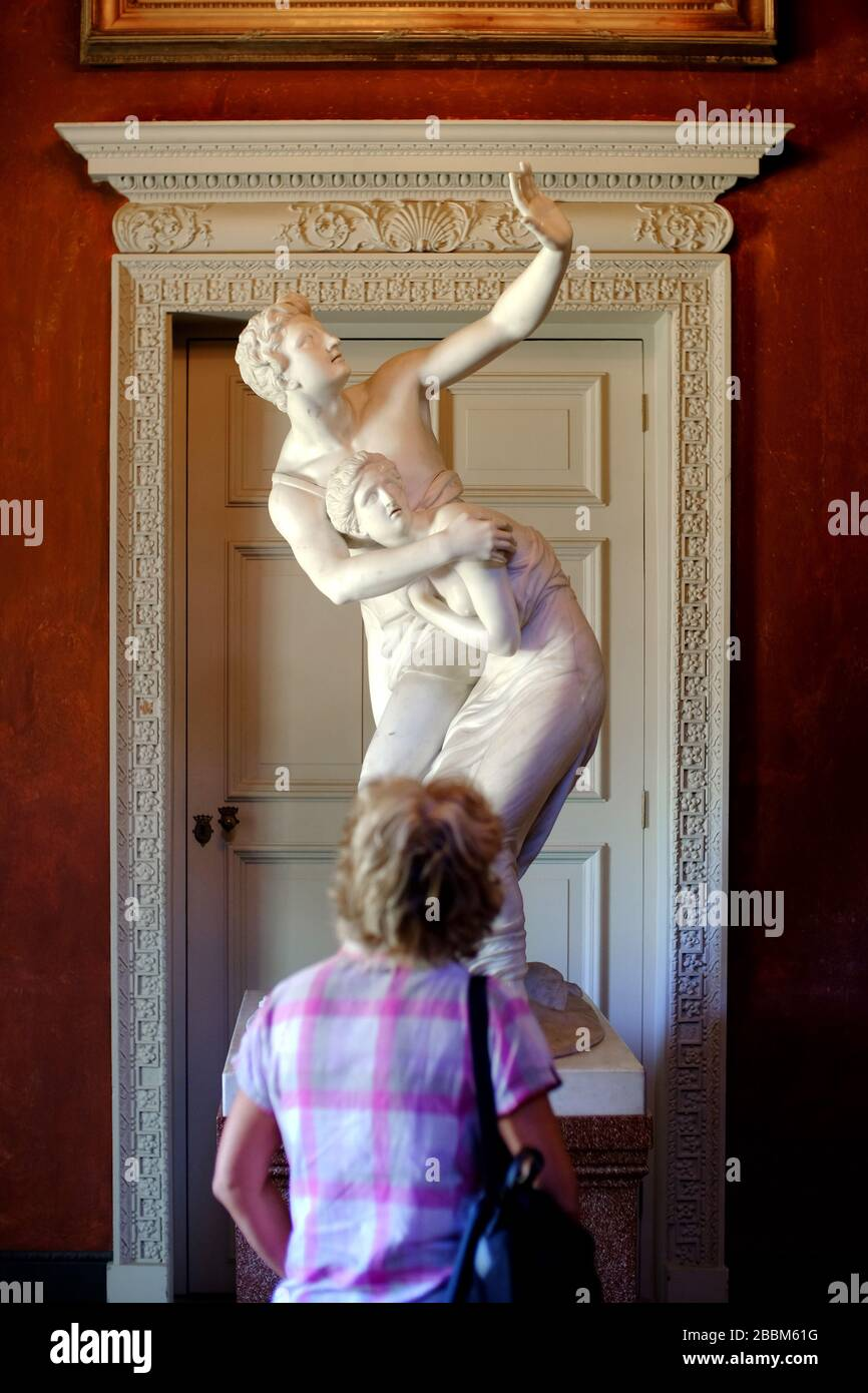 Woman viewing a classical marble sculpture in an art gallery / museum showing traditional gender roles. Stock Photo