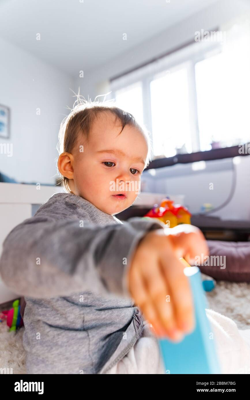 Portrait of one year old baby girl indoors in bright room playing by herself Stock Photo