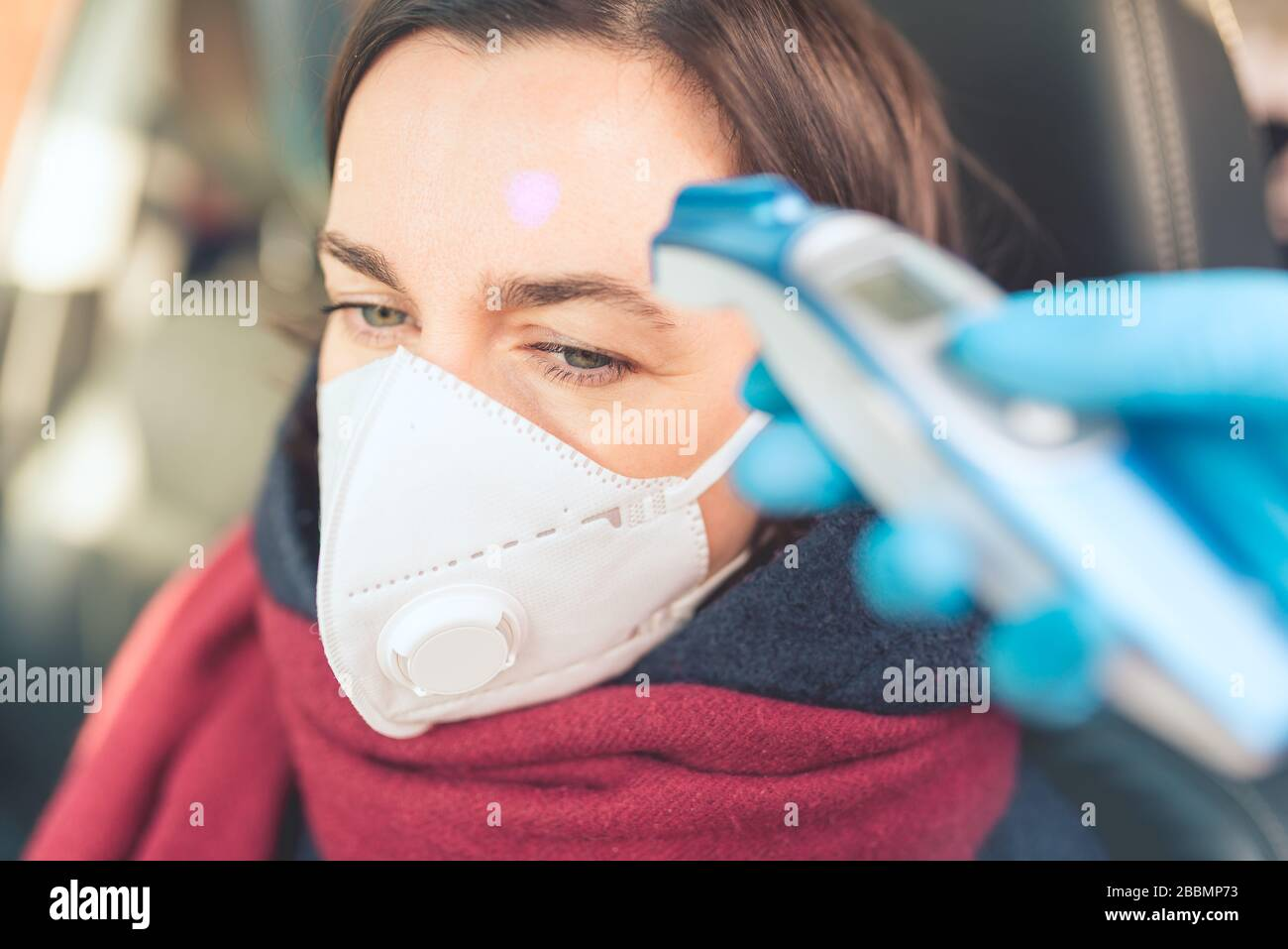 Temperature check point - the woman behind the wheel of the car in an anti-virus mask is subjected to temperature measurement. Coronavirus concept - r Stock Photo