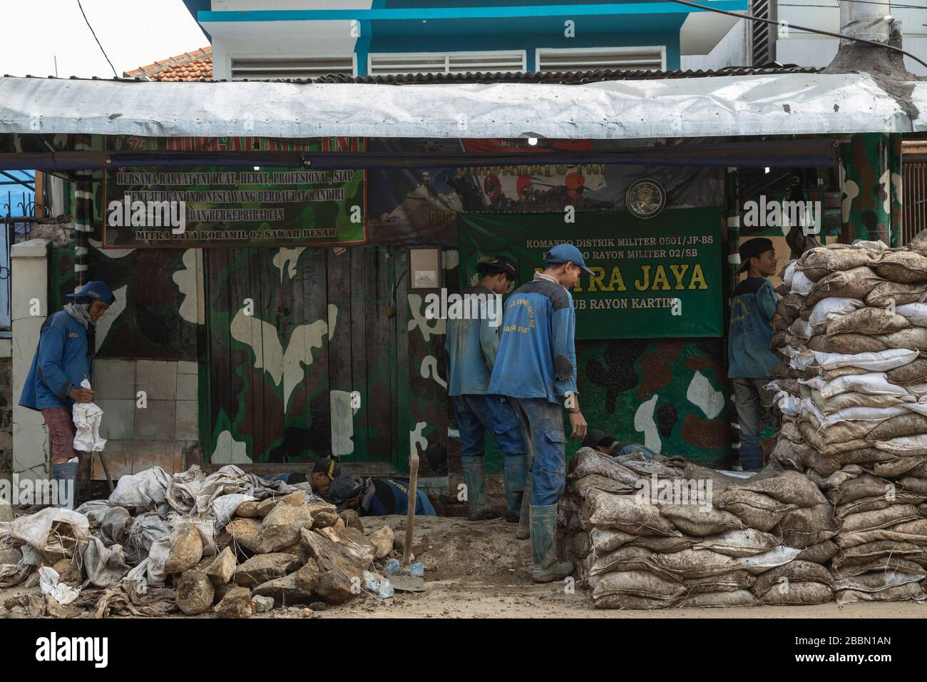 Jakarta, Indonesia - July 13, 2019: A group of maintenance workers work rudimentaryly digging ditches, filling sacks with soil and fix sewage pipes. Stock Photo