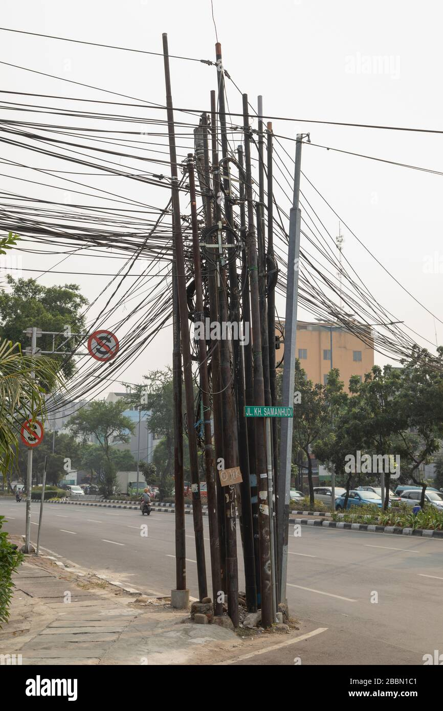 Jakarta, Indonesia - July 13, 2019: Poles loaded with a tangle of black underground electrical cables, on the streets of Central Jakarta. Stock Photo