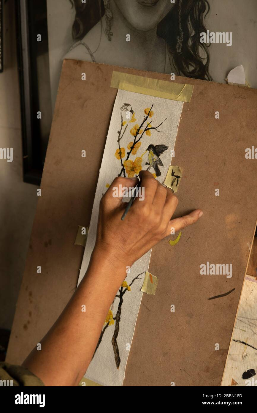 Jakarta, Indonesia - July 13, 2019: A local painter and cartoonist paints a blooming branch with birds with acrylics in his small studio. Stock Photo