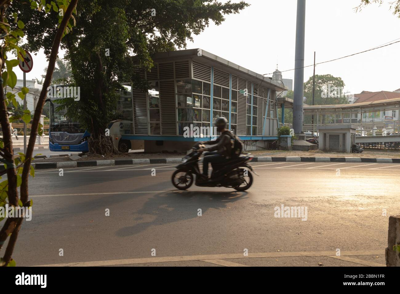 Jakarta, Indonesia - July 13, 2019: A motorcyclist passes in front of the bus stop from the TransJakarta public transport system. Stock Photo