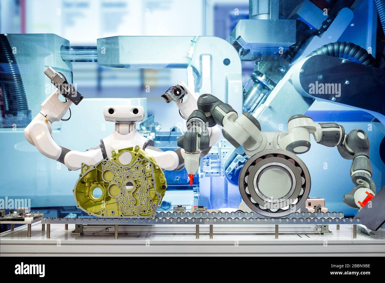 Two industrial robotics working automation with auto parts and spherical roller bearing via a conveyor belt, on machine blue tone color background Stock Photo