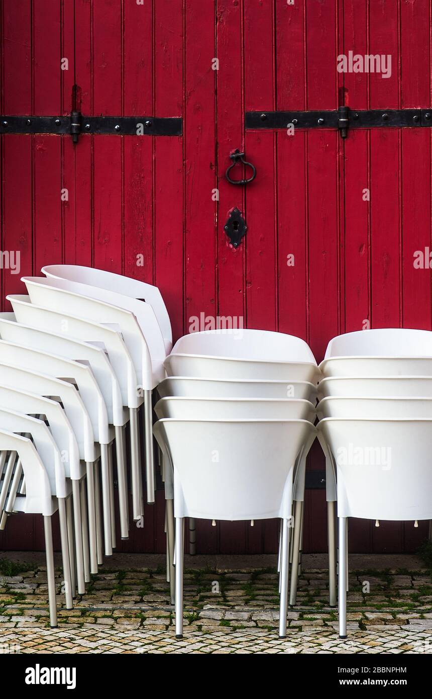 Groups of white chairs stacked together againts a red wooden door Stock Photo