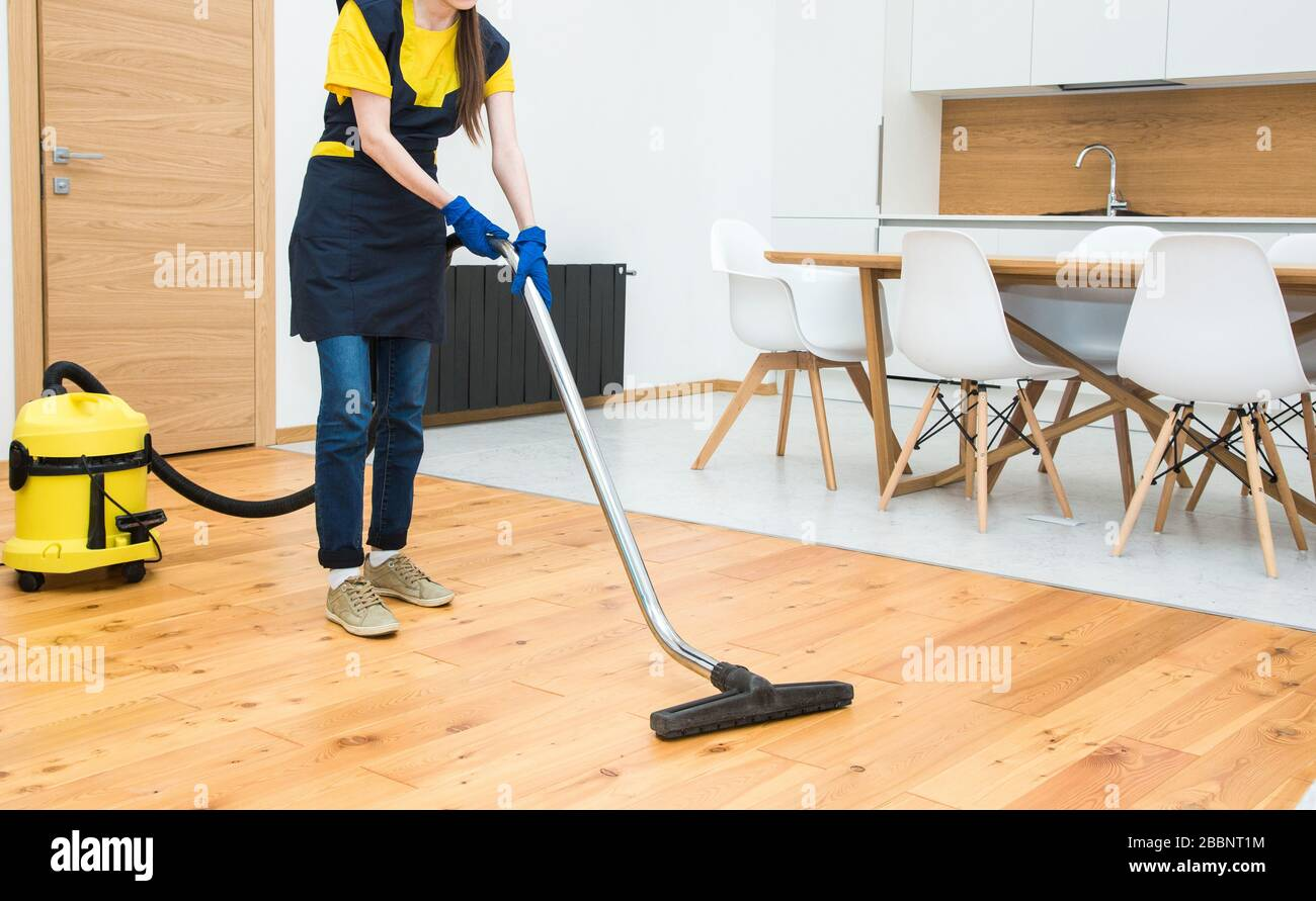 professional cleaning service. woman in uniform and gloves does the cleaning in a cottage. the worker vacuums the floor with professional equipment Stock Photo