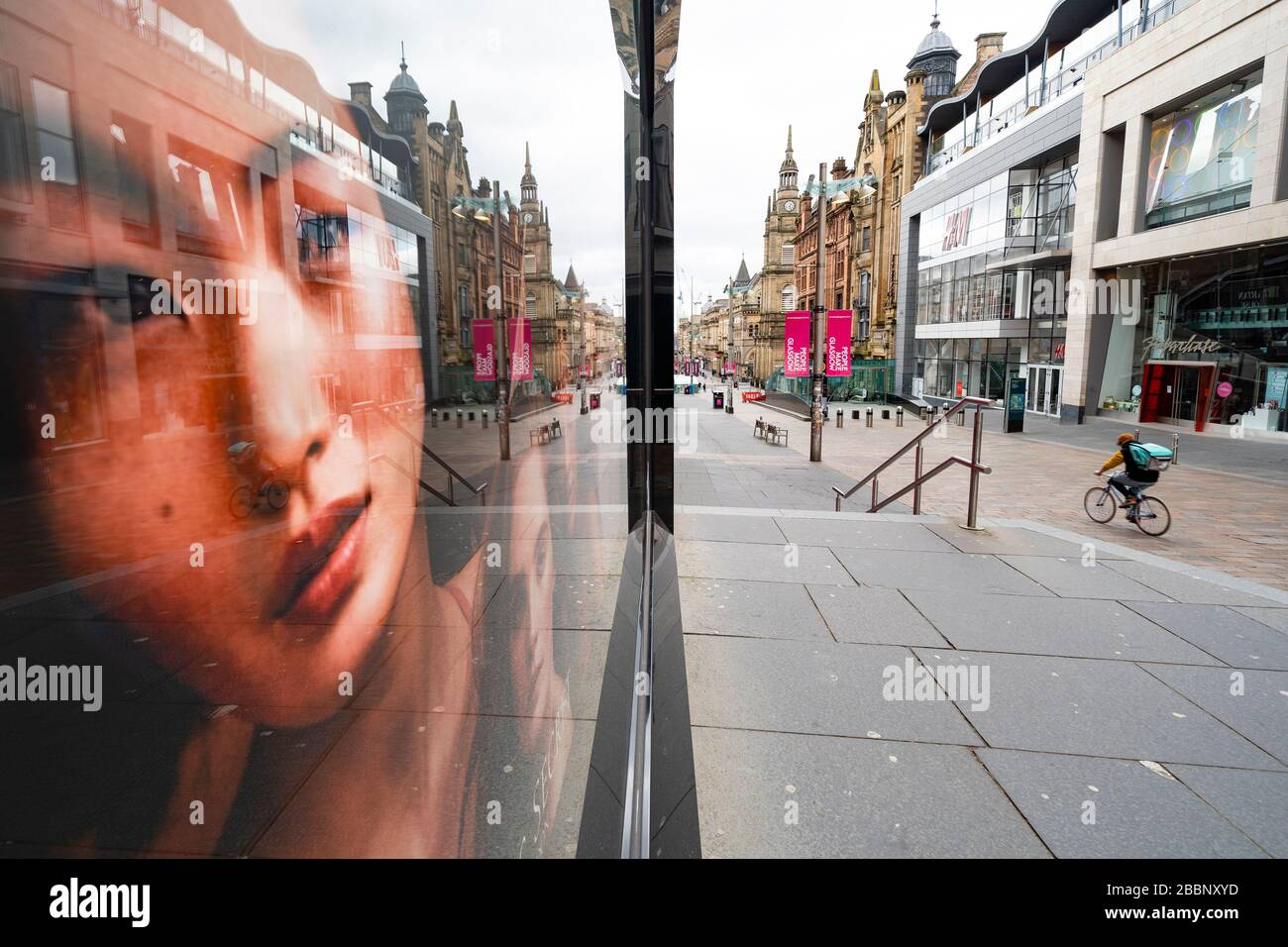 Glasgow, Scotland, UK. 1 April, 2020. Effects of Coronavirus lockdown on streets of Glasgow, Scotland. Photo of model in Victoria's Secret shop looks out on a deserted Buchanan Street with a lone Deliveroo cyclist riding past .Iain Masterton/Alamy Live News Stock Photo