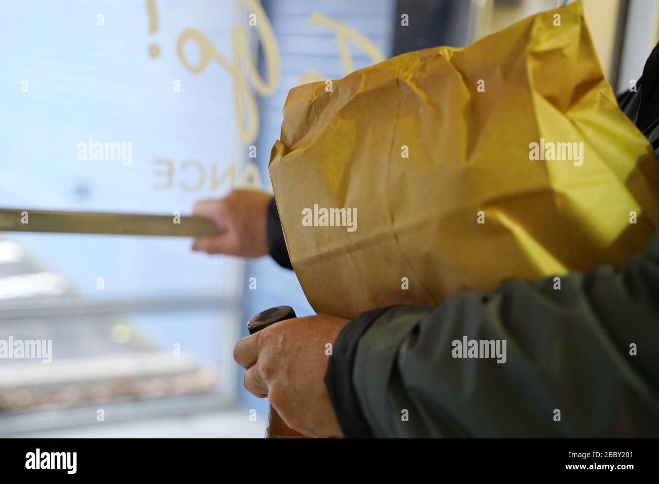 Man pushes the door handle to exit the restaurant after picking up a food order (focus on edge of paper bag) Stock Photo