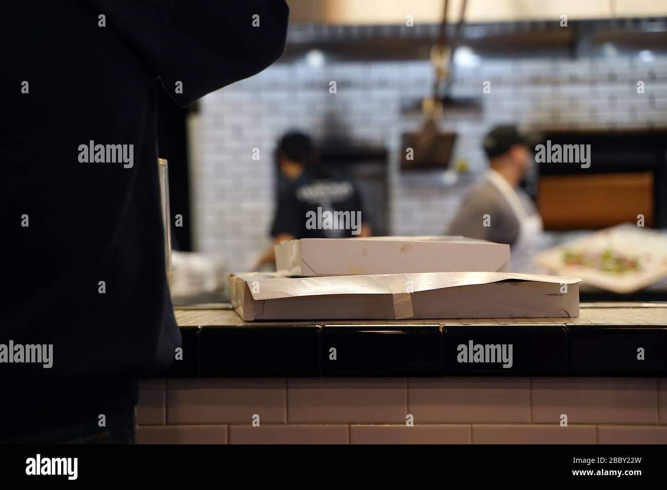 Manchester, CT / USA - March 12, 2020: Two pizza boxes wait on the counter for pickup and delivery Stock Photo