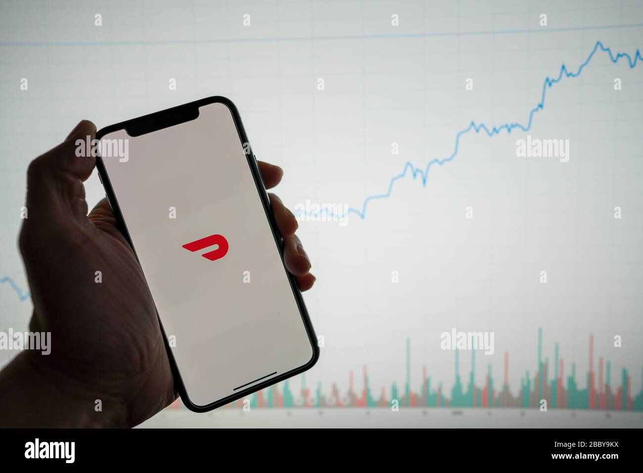 Doordash app on phone with white financial stock chart with price rising upward positive in background Stock Photo
