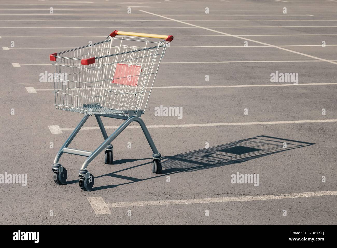 Empty grocery cart in an empty parking lot near a supermarket. Financial crisis, quarantine, lack of money concept Stock Photo
