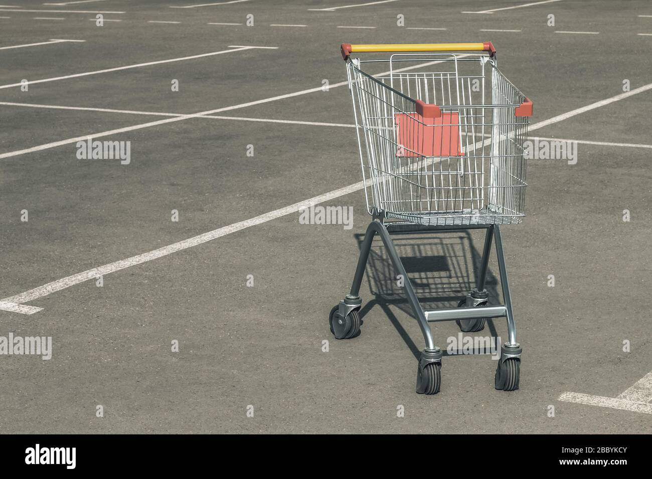 Single empty grocery cart in an empty parking lot near a supermarket with copy space. Crisis, panic, lack of money, unemployment concept Stock Photo