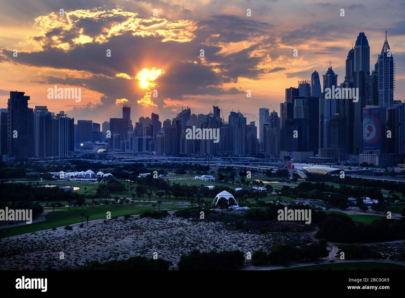 Sunset viewed from 17th floor apartment in Dubai, United Arab Emirates, with golf course in the foreground. Stock Photo