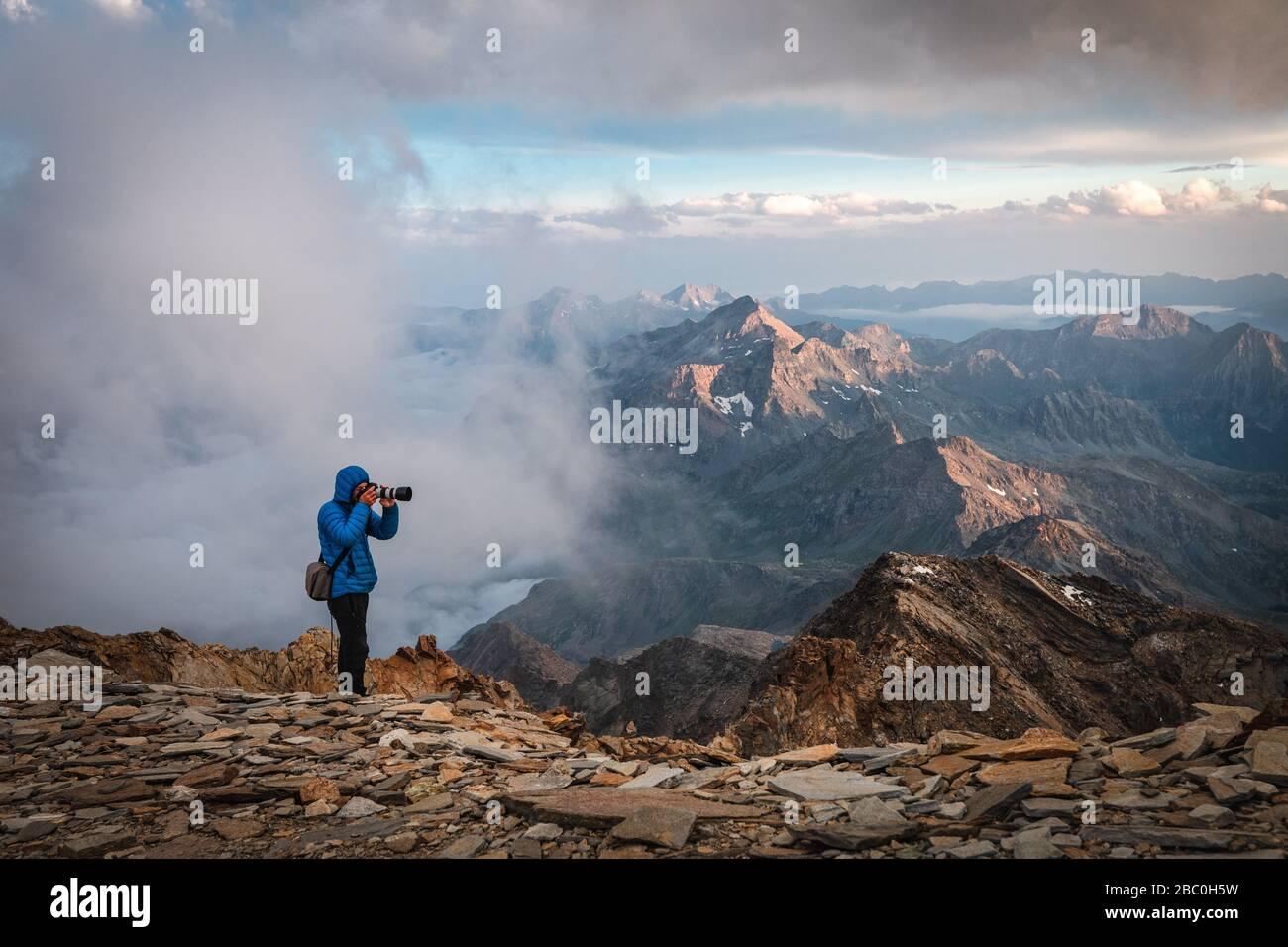 PHOTOGRAPHER TAKING ADVANTAGE OF THE SUNSET NEAR THE QUINTINO SELLA REFUGE, MONTE ROSA, GRESSONEY-LA-TRINITE, AOSTA VALLEY, ITALY Stock Photo