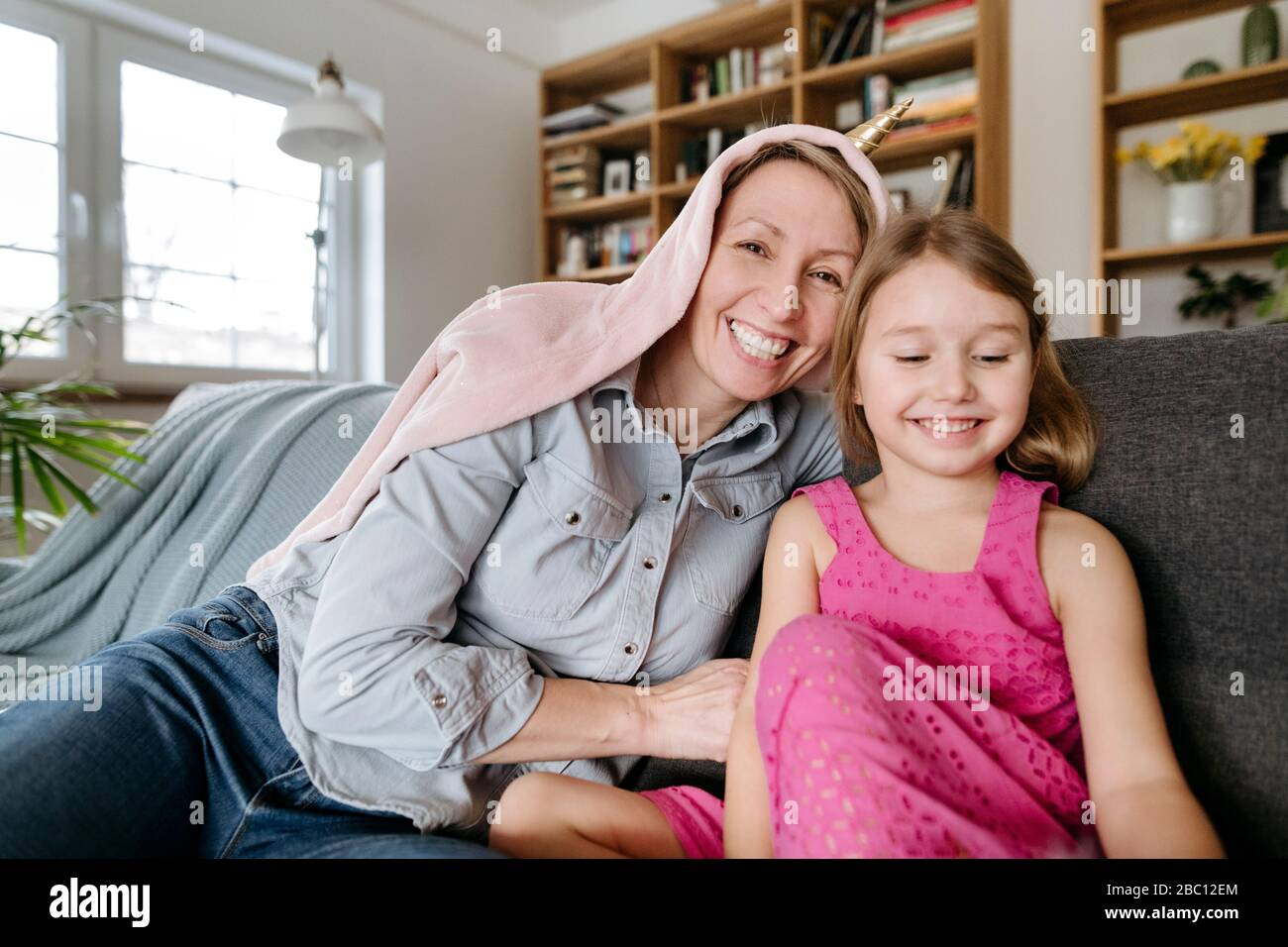 Portrait of happy mother and her little daughter sitting together on the couch having fun Stock Photo