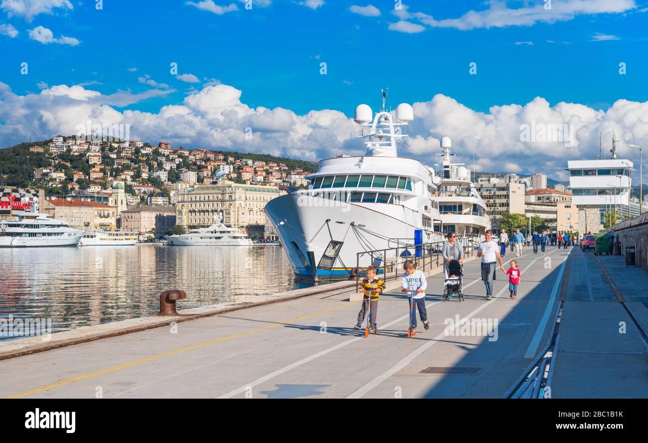Rijeka - June of 2012, Croatia: View of Rijeka port, kids ride scooters on the pier Stock Photo
