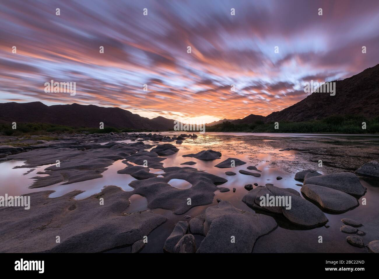 A Beautiful Long Exposure Landscape Taken After Sunset With Mountains And The Orange River With Dramatic Orange Moving Clouds Reflecting In The Water Stock Photo Alamy