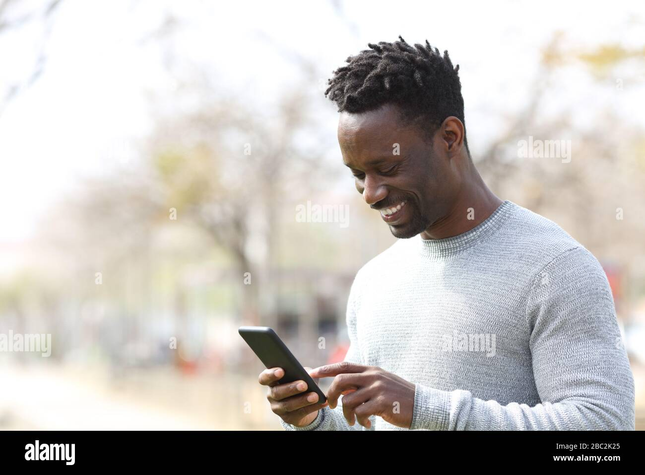 Happy black man using smart phone walking in a park a sunny day Stock Photo