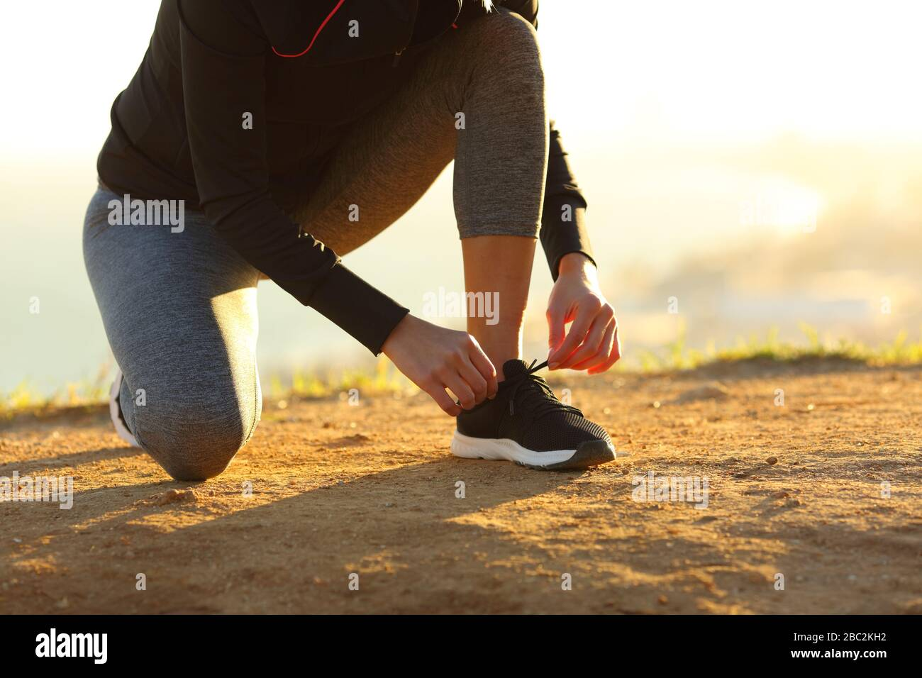 Runner woman hands tying shoelaces of shoes on the ground at sunset Stock Photo
