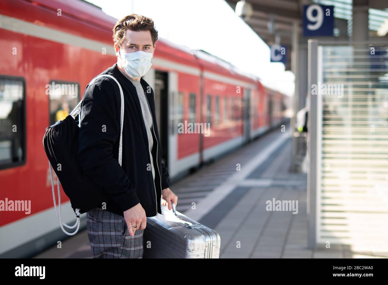Man with a suitcase on the platform, he has a face mask and gloves against infection with the corona virus Stock Photo