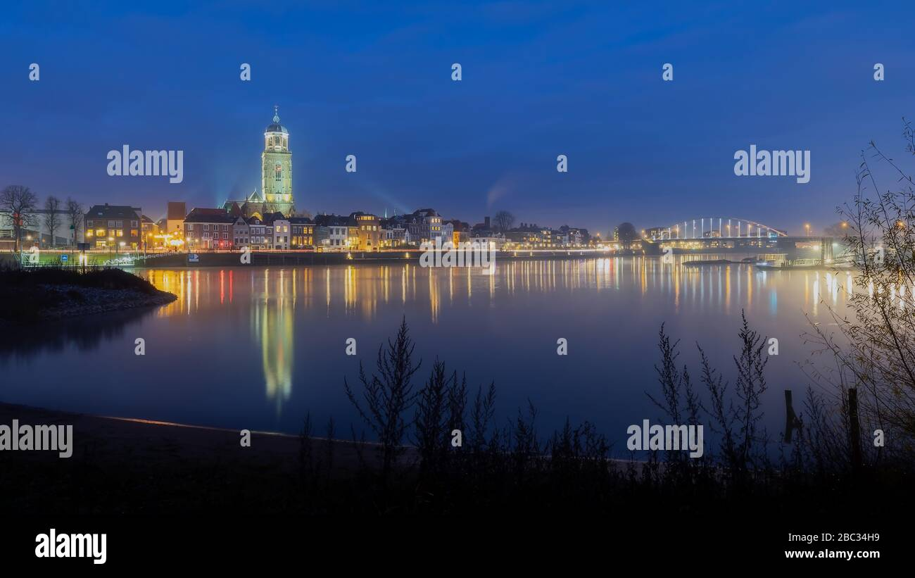 Deventer, The Netherlands - Decembre 1, 2019; View on the city skyline of Deventer beginning of the evening reflection in the river IJssel Lebuinus ch Stock Photo