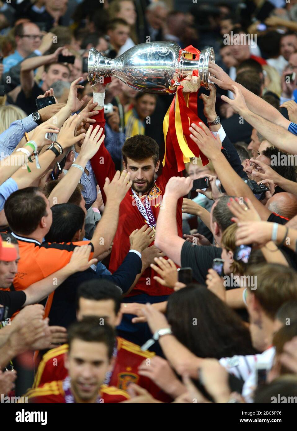 Spain's Gerard Pique carries the UEFA European Championship trophy down the steps after the game, as he is mobbed by fans Stock Photo