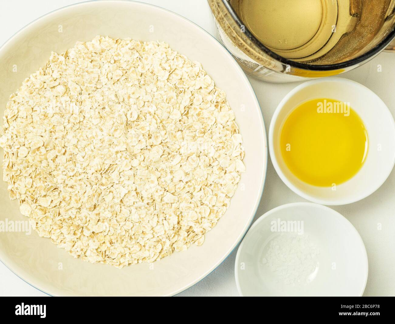 Rolled oats water rapeseed oil and sea salt ingredients for making dairy alternative oat cream on a white tablecloth Stock Photo