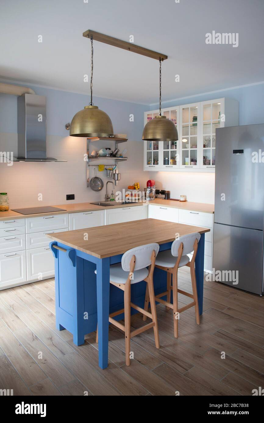 White Bright Kitchen With Blue Island And Double Brass Pendant Lights Vertical Shot Stock Photo Alamy