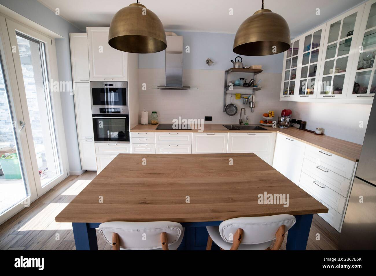 White Bright Kitchen With Blue Island And Double Brass Pendant Lights Central View With Kitchen Island In The Foreground Stock Photo Alamy