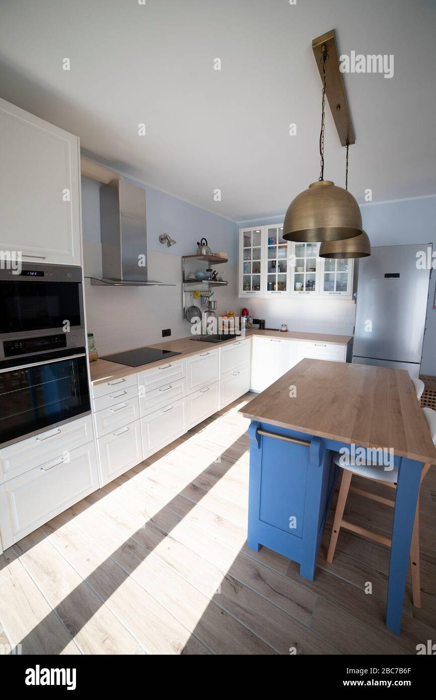 White Bright Kitchen With Blue Island And Double Brass Pendant Lights Vertical Shot Side View Stock Photo Alamy