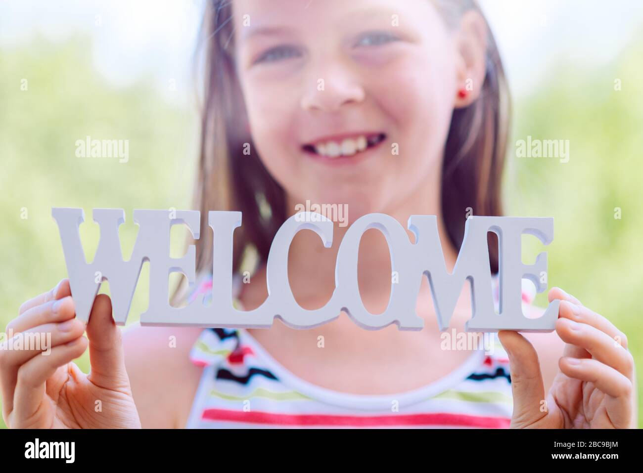 Little laughing girl holding the words WELCOME in her hands - shallow depth of field - focus on lettering Stock Photo