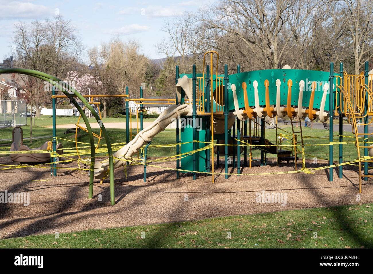 Berks County, Pennsylvania, USA-April 2, 2020: Public playground closed with caution tape so children do not play on equipment to prevent spread of co Stock Photo