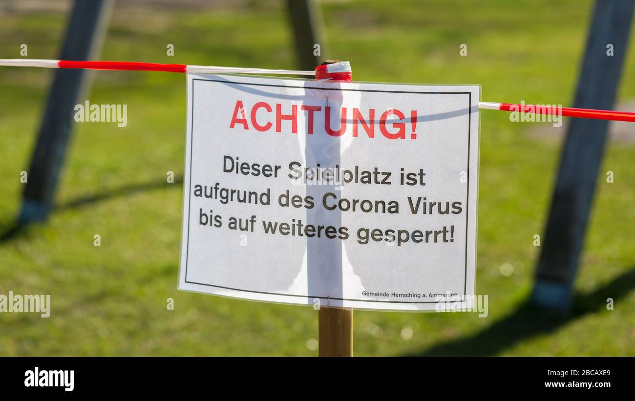 Close up of sign at closed off playground (Spielplatz). With a typical german word: Achtung! (Attention!). Restrictions due to Covid-19 / Coronavirus. Stock Photo