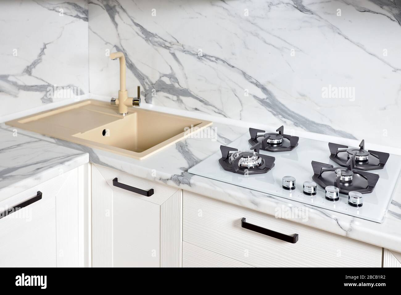 Modern design chrome water tap over stainless steel kitchen sink on table top made of white stone marble or granite. Stock Photo
