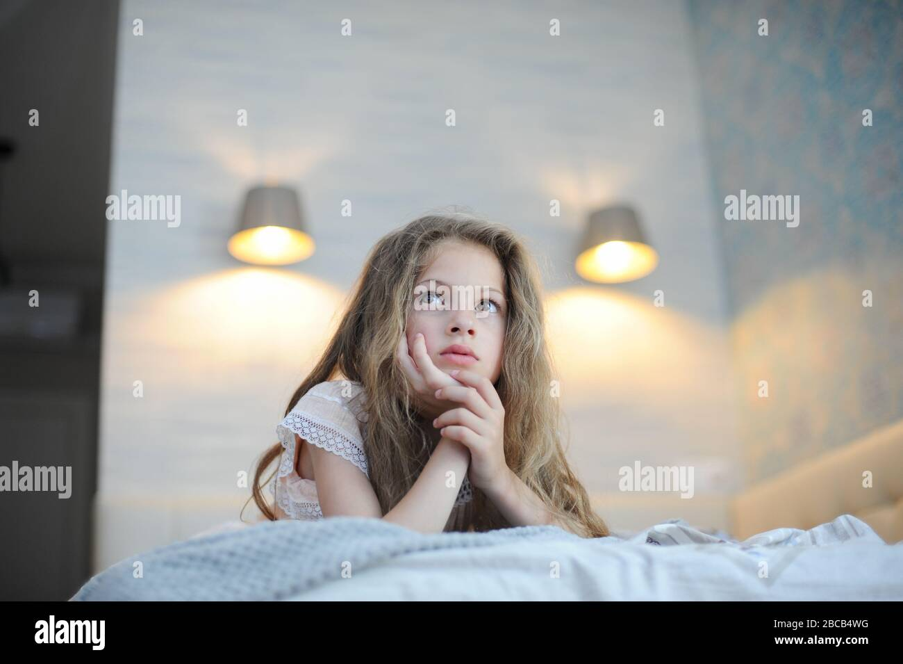 Beautiful Little Girl With Long Hair Lying On Bed In Bedroom Indoors At Home Watching Tv During Self Isolation Quarantine Stock Photo Alamy