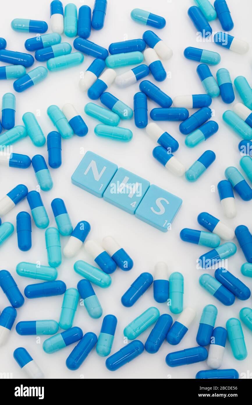 NHS letters tiles & assorted blue pills. Metaphor NHS in Covid 19 pandemic, NHS heroes, NHS prescriptions, UK National Health Service, medicine in UK Stock Photo