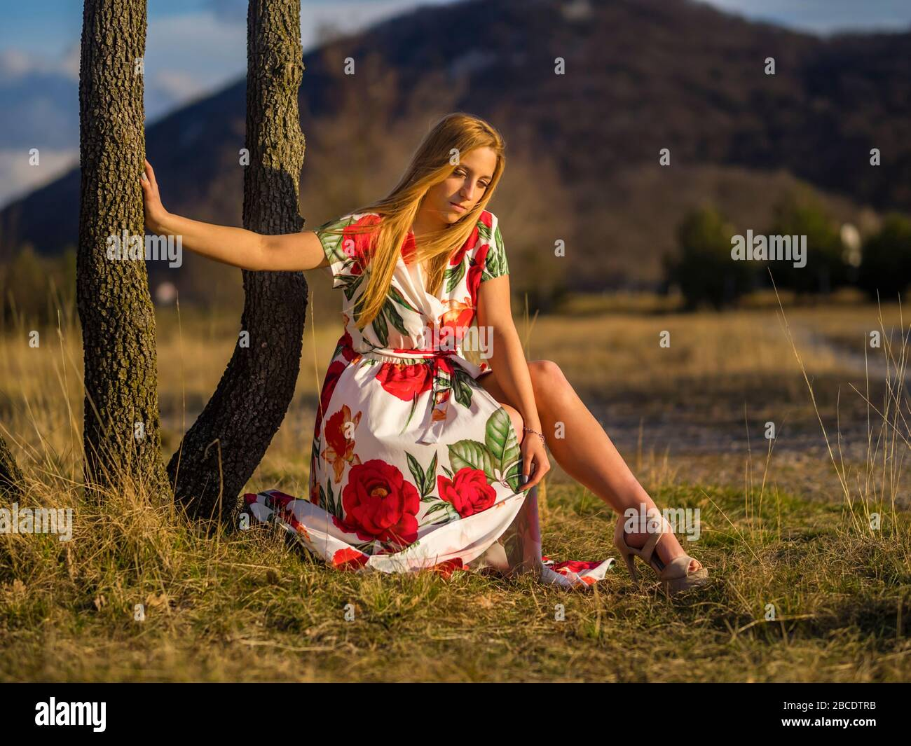 Teenage female person aka young woman trying to cover leg legs because of gust wind windy looking down serious setting sun sunset warm light Stock Photo